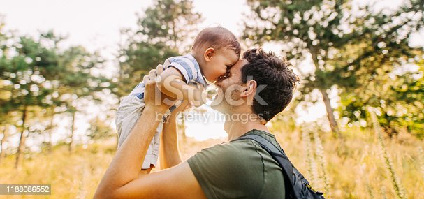 Photo of baby boy and his daddy in the nature