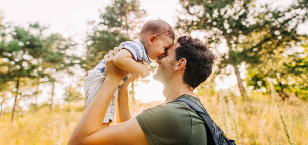 Baby boy with daddy in the nature stock photo