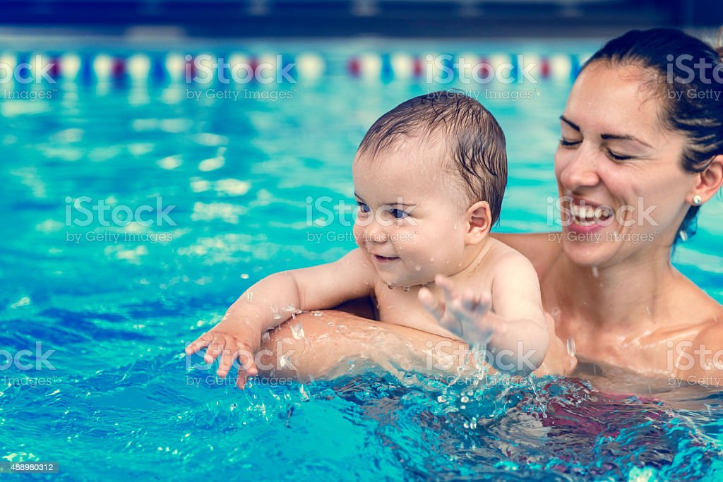 Baby boy with his mother in the pool stock photo