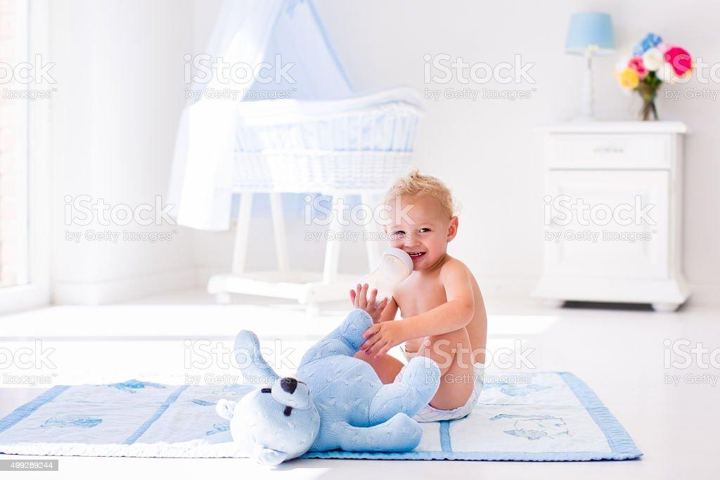 Baby boy with milk bottle in sunny nursery foto