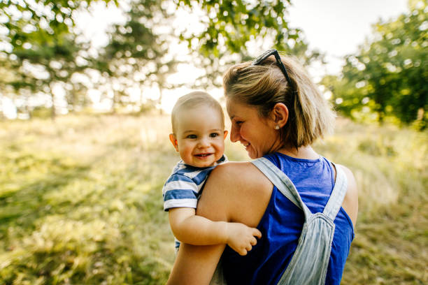 Baby boy with mommy in the nature stock photo