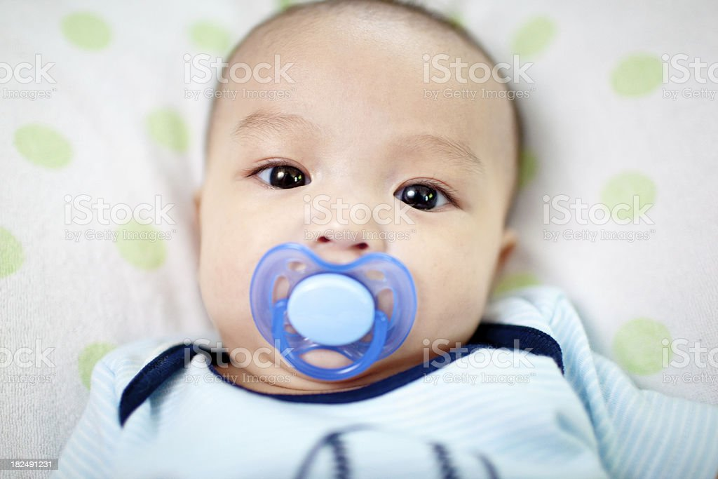 baby boy with pacifier looking into camera stock photo