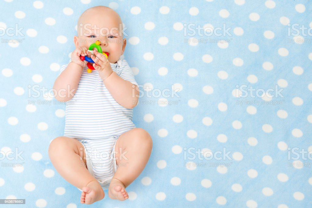 Baby Boy with Teether Toy on Blue Background, Happy Infant Kid Boy in Bodysuit Lying over Blue Blanket stock photo