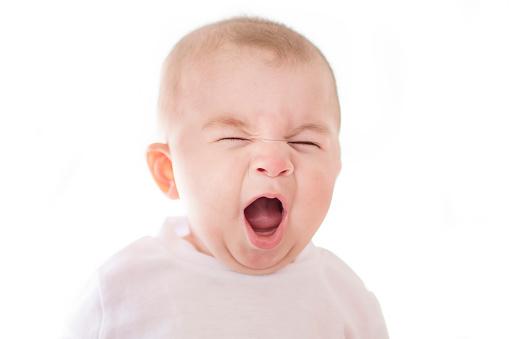 istock Baby boy yawns isolated on white background 1078559732