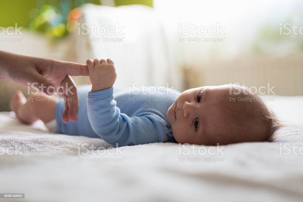 Baby boy`s holding mommys finger stock photo
