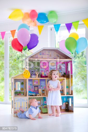 istock Baby brother and sister playing with a doll house 504782075