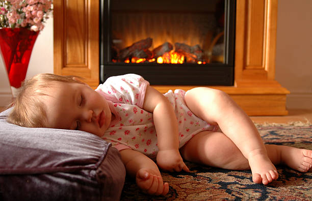 Baby by Fire stock photo