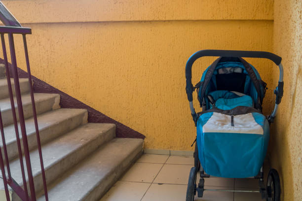Baby carriage standing on the staircase in the stairwell Baby carriage standing on the staircase in the stairwell baby carriage stock pictures, royalty-free photos & images