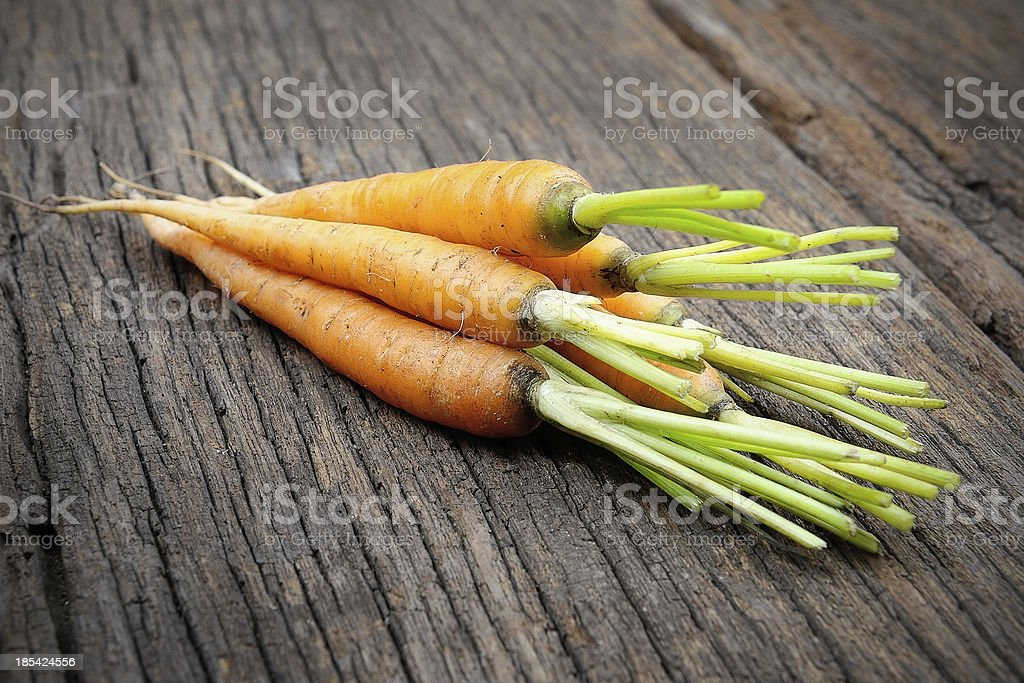 closeup baby carrots on wooden table