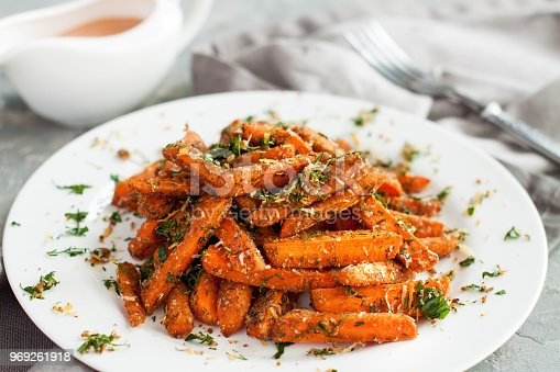 Baby carrots roasted with parmesan and herbs served with sauce on grey table