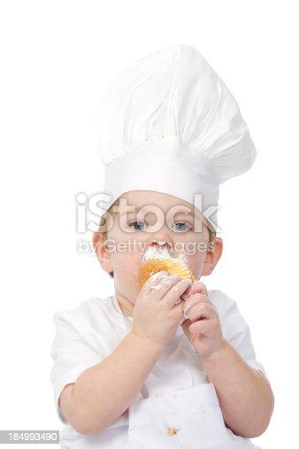 istock baby chef eating cupcake 184993490
