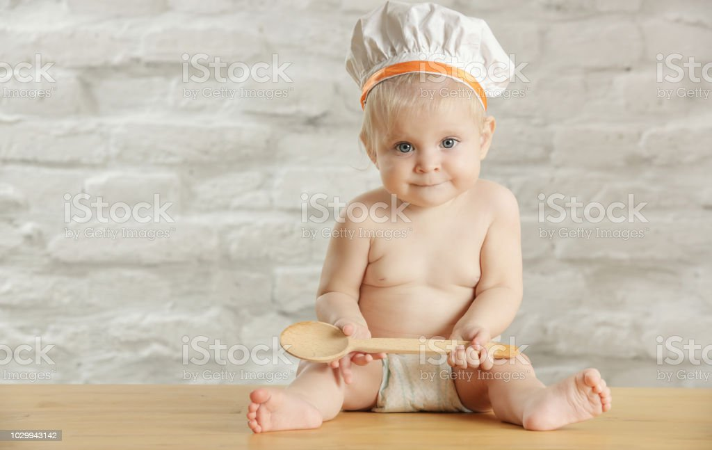 Baby chef - indoor portrait of an adorable baby with chef hat and wooden spoon stock photo