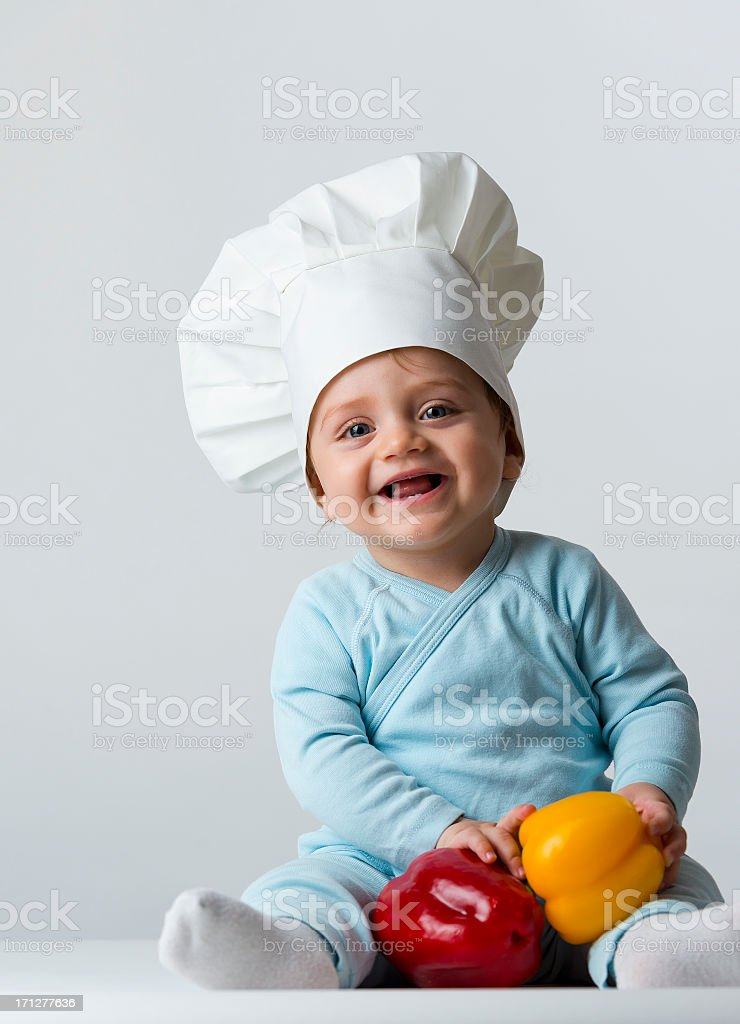 Baby chef looking at the camera and laughing stock photo