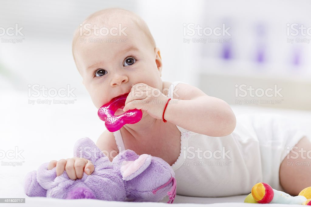 Baby chewing a teething toy on bed. stock photo