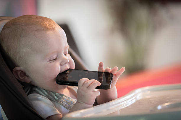 Baby Chewing Mobile Phone stock photo