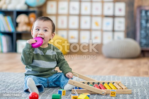 A young Asian boy is sitting on the carpet in a daycare center. He is is trying to put a toy in his mouth.