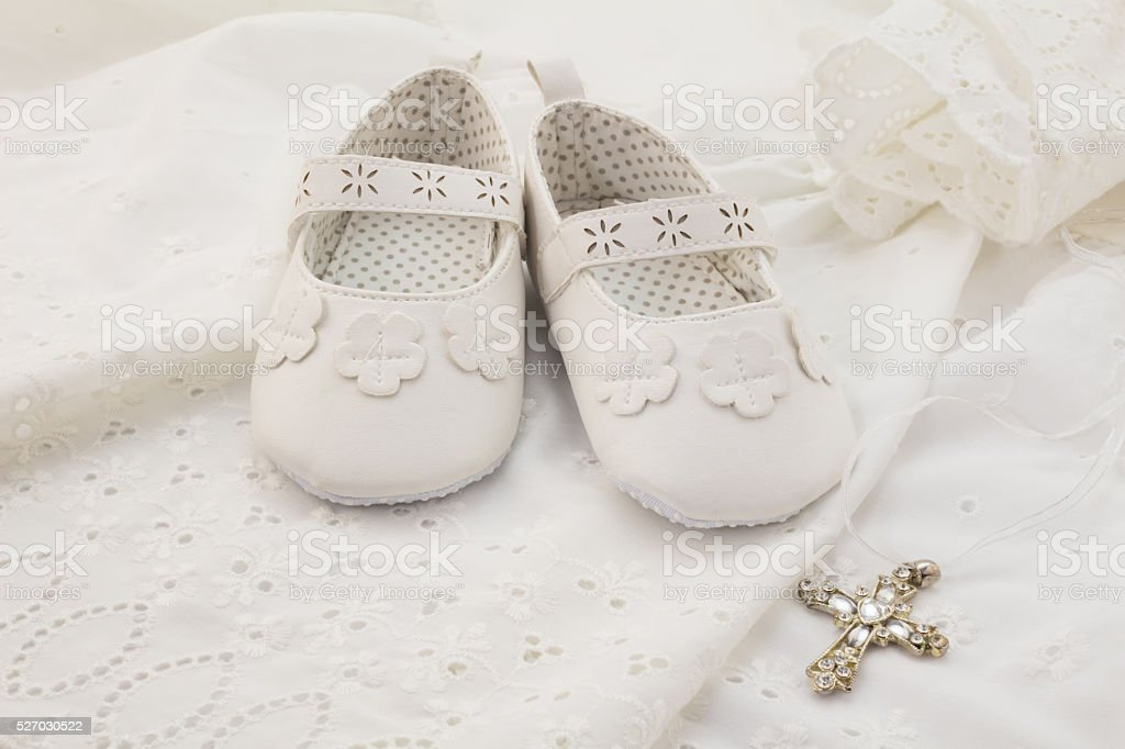 Baby christening white shoes with cross pendant on white stock photo