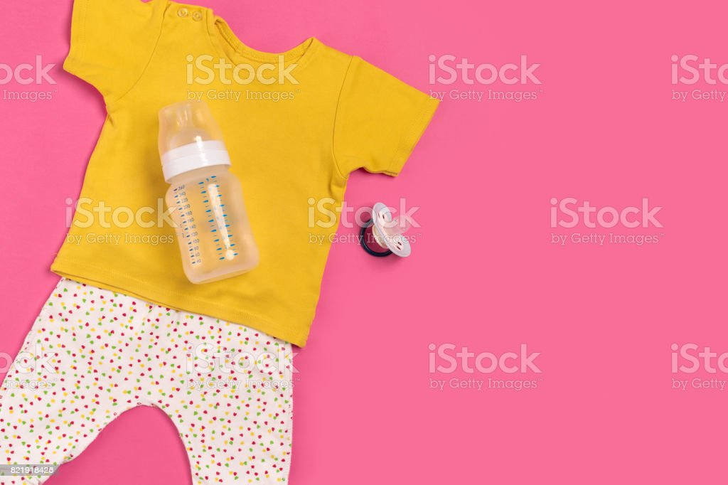 Baby clothes and accessories on pink background. Top view stock photo