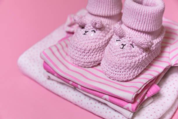 baby-kleidung und häkeln schuhe für neugeborene mädchen auf einem rosa hintergrund - babyschuhe nähen stock-fotos und bilder