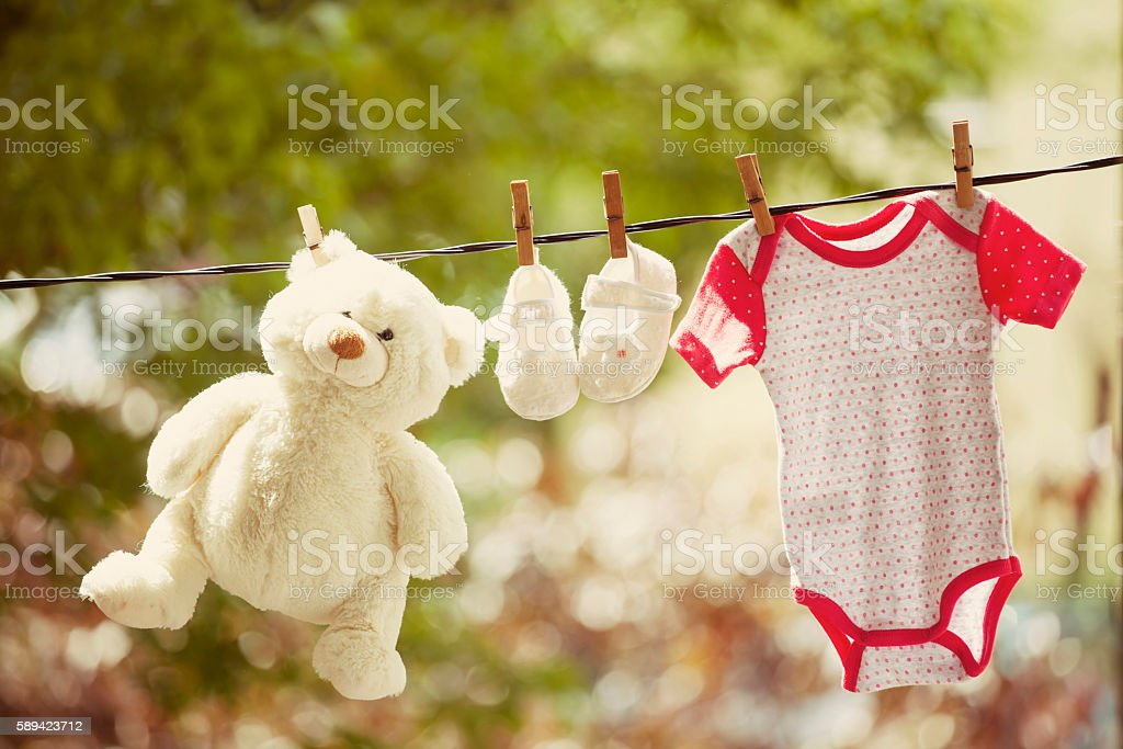 Baby clothes and teddy bear hanging on the clothesline stock photo
