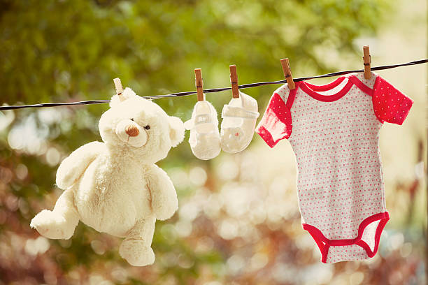 Baby clothes and teddy bear hanging on the clothesline Baby clothes and teddy bear hanging on the clothesline - family concept kids cleaning up toys stock pictures, royalty-free photos & images
