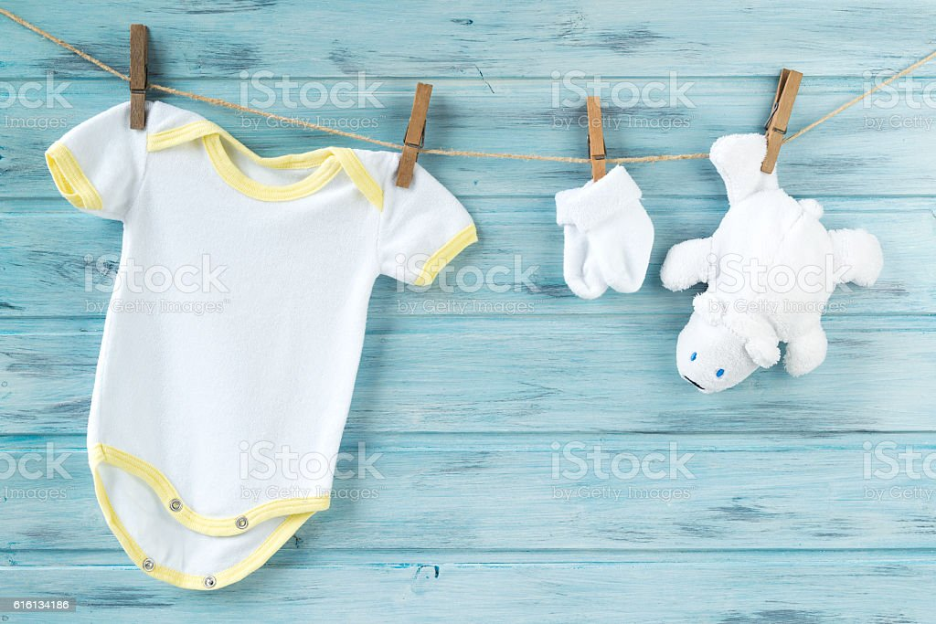 Baby clothes and white bear toy on a clothesline - foto de acervo