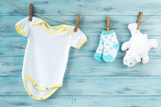 Baby clothes and white bear toy on a clothesline stock photo