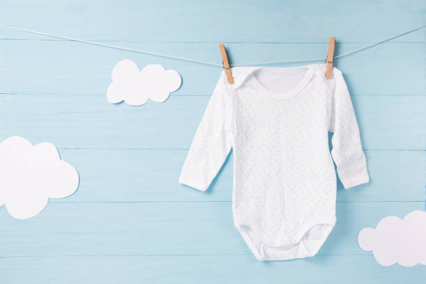Baby clothes and white clouds on a clothesline, blue background stock photo