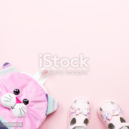 Baby clothes collection flat lay with sandals, backpack on pastel background. Top view
