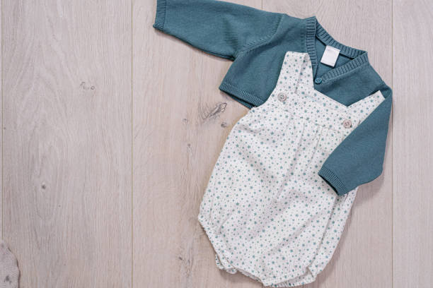 concepto de ropa de bebé. traje blanco y azul para niño sobre fondo de madera - foto de stock