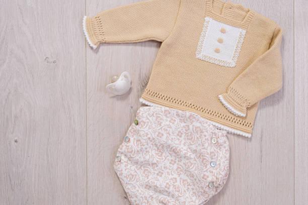 concepto de ropa de bebé. traje blanco y marrón para niño sobre fondo de madera - foto de stock