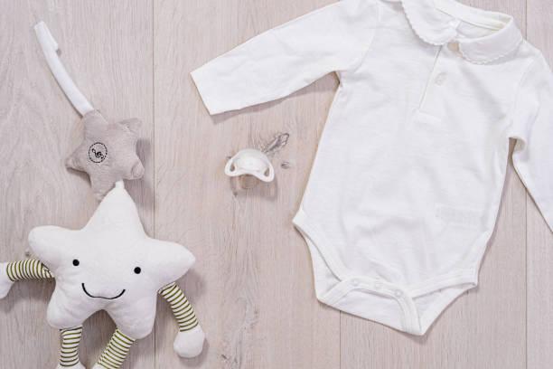 concepto de ropa de bebé. traje blanco para niño y niña y un chupete bebé sobre fondo de madera - foto de stock