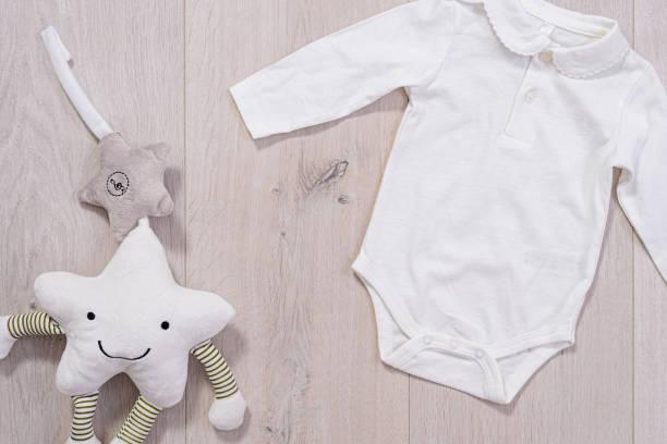 concepto de ropa de bebé. traje blanco para niño y niña sobre fondo de madera - foto de stock