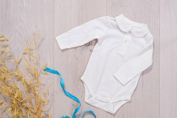 concepto de ropa de bebé. traje blanco para niño sobre fondo de madera - foto de stock