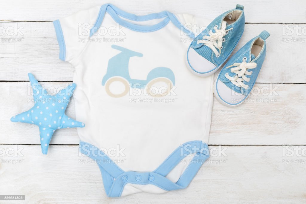 Baby clothes for little boy  on wooden background. Flat lay stock photo