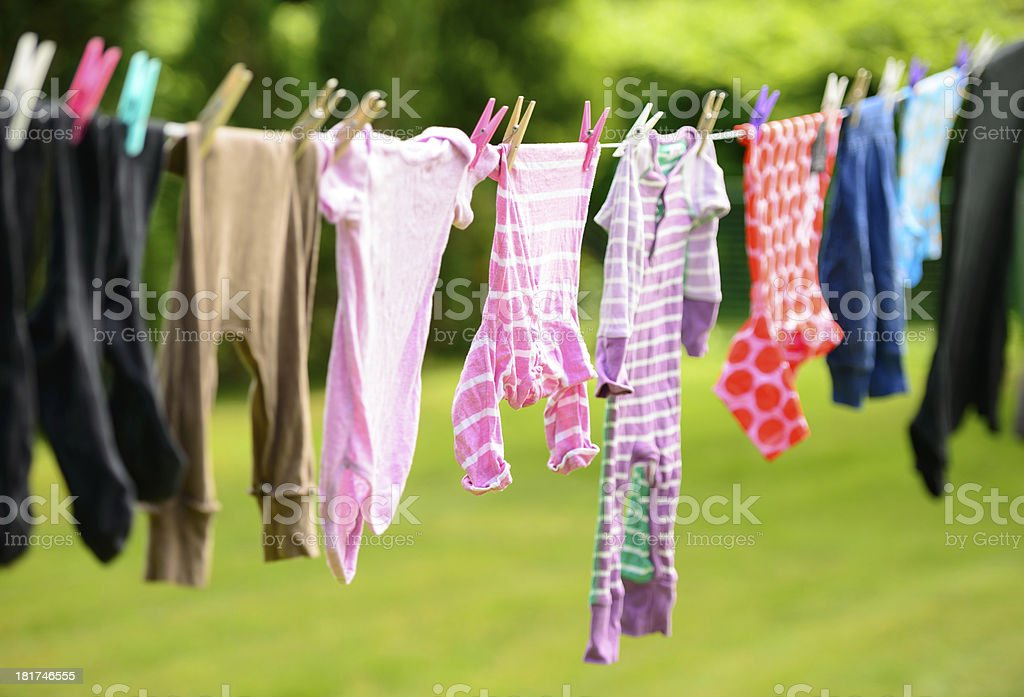 Baby clothes hanging on a line stock photo