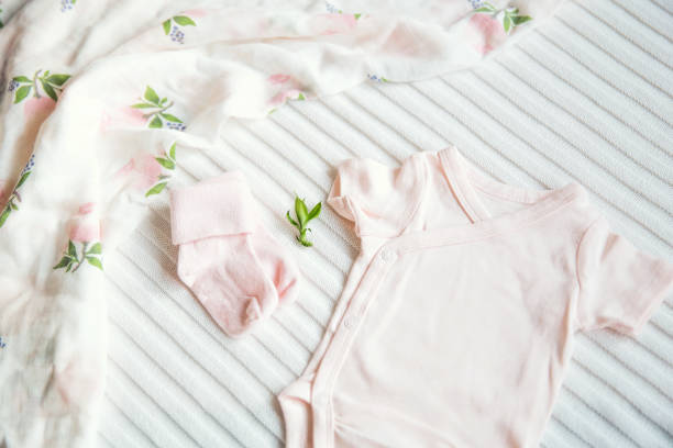 Baby clothes on light pastel fabric background. stock photo