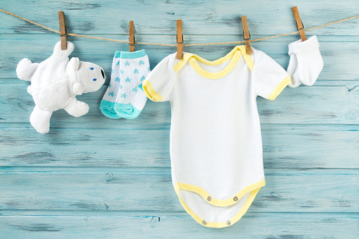 istock Baby clothes, onesie, socks, white bear toy on a clothesline 622909152