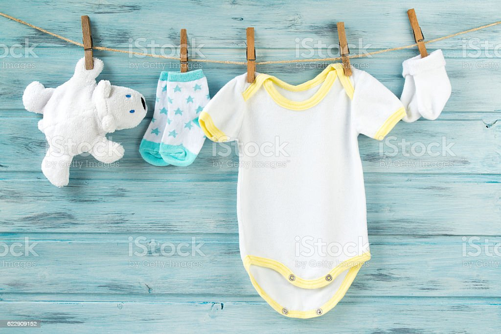 Baby clothes, onesie, socks, white bear toy on a clothesline stock photo