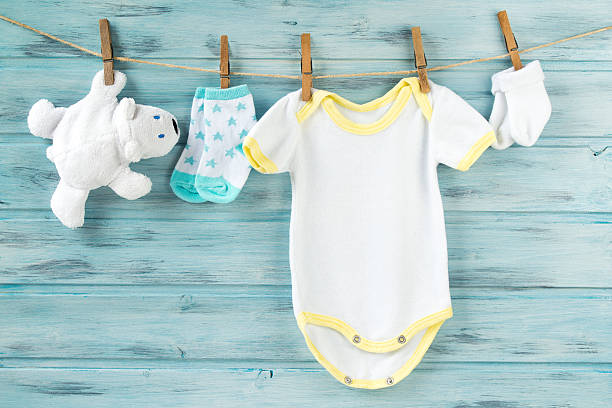 baby clothes, onesie, socks, white bear toy on a clothesline - blaubär stock-fotos und bilder