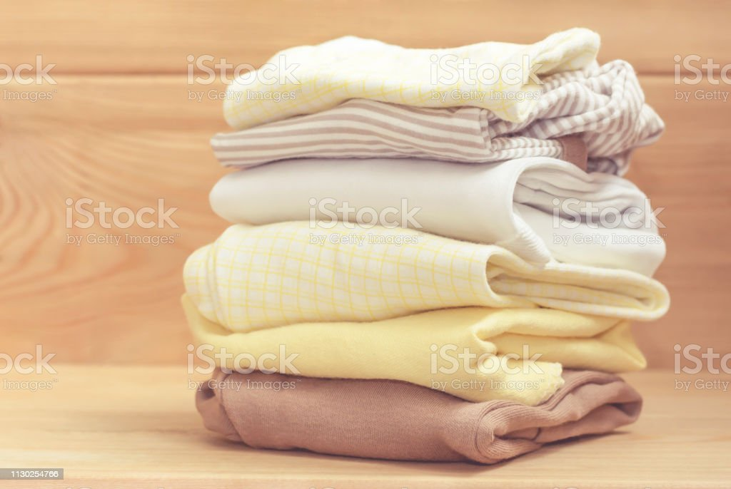 Baby Clothes Stack For Newborn On Wooden Background In Pastel