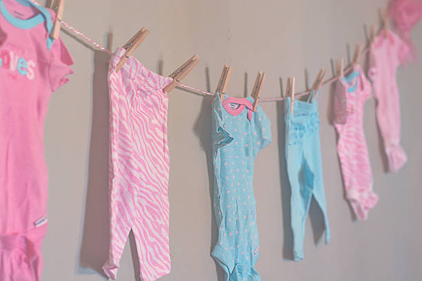 Baby clothes with clothes pins stock photo