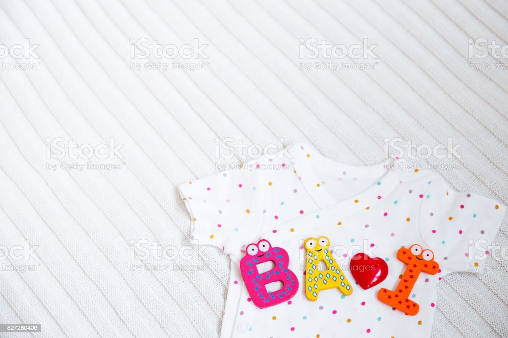 edacfac38bf8 Baby Clothes With Toy Letters On White Fabric Background stock photo ...