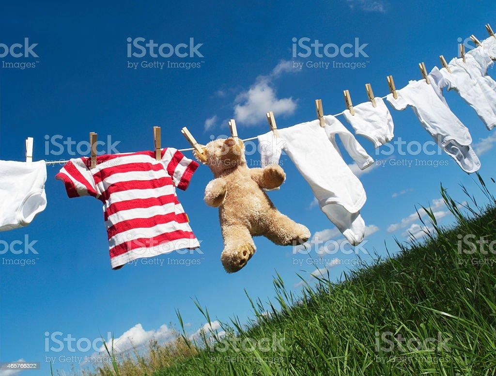 Ropa de bebé sobre una cuerda de tender la ropa foto de stock libre de derechos