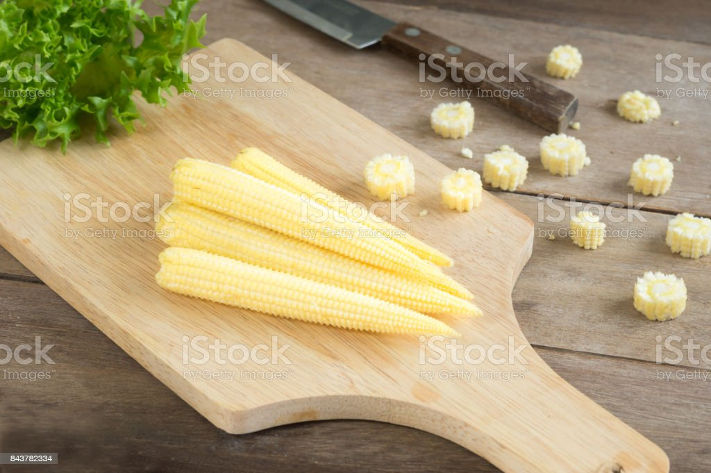 Baby corns and knife on cutting board,food ingredient. stock photo