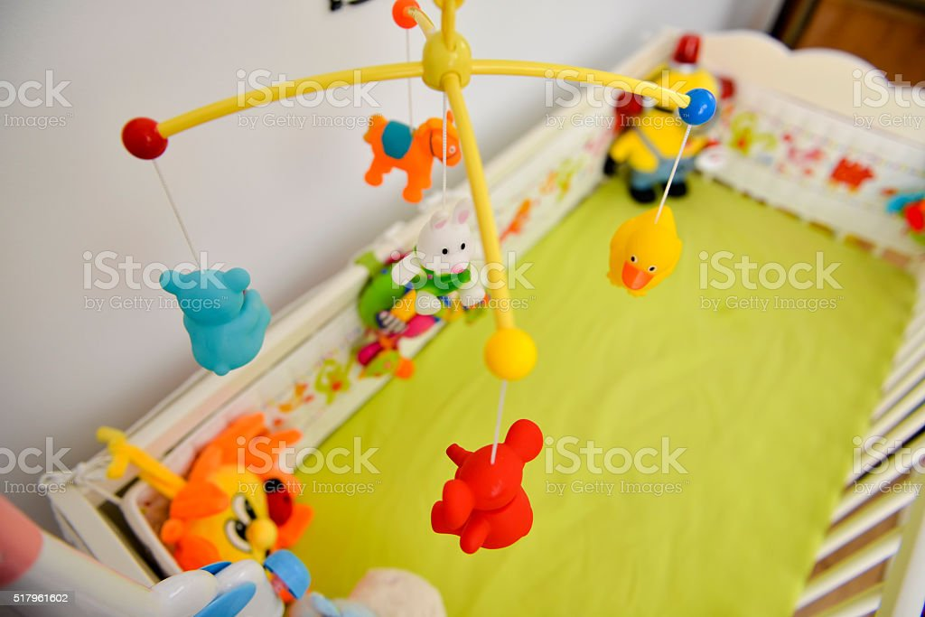 Baby cot with colorful toys hanging stock photo