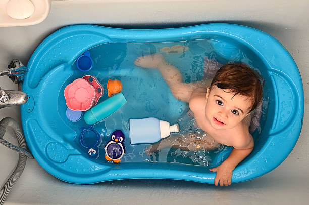 A baby covered in soap during bath time stock photo