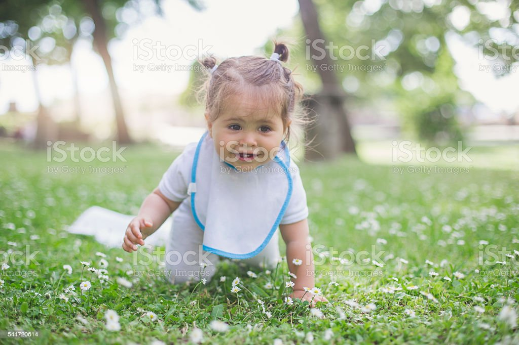 baby crawling on a grass for a first time stock photo