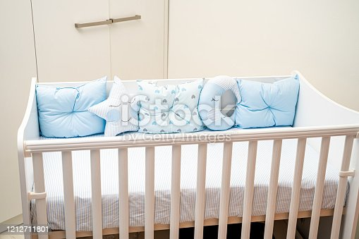Baby crib with blue pillows. The scene is situated indoors in family bedroom. The picture is taken with Sony A7III camera.