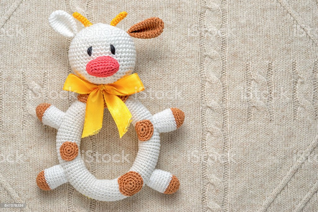 Baby crochet homemade toy cow on knitted background. stock photo